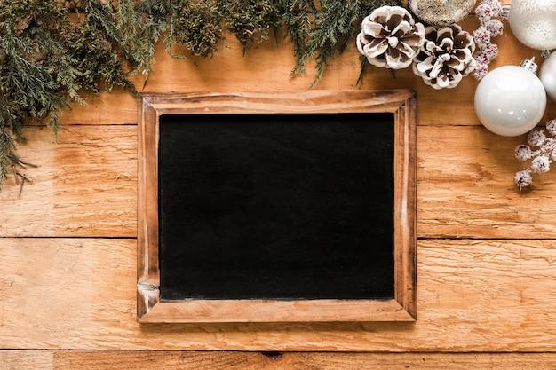 Fotorahmen in der nähe von nadelbäumen und weihnachtskugeln Kostenlose Fotos