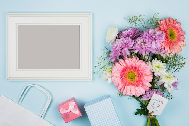 Fotorahmen nahe blumenstrauß von frischen blumen mit titel auf tag nahe paket, geschenk und notizbuch Kostenlose Fotos