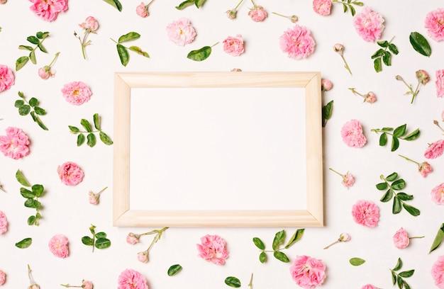 Fotorahmen zwischen sammlung rosa blumen und grünen blättern Kostenlose Fotos