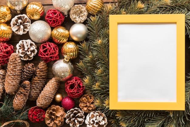 Fotorahmen zwischen tannenzweigen, ziergegenständen und weihnachtskugeln Kostenlose Fotos