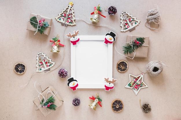 Fotorahmen zwischen weihnachtsdekorationen und geschenkboxen Kostenlose Fotos