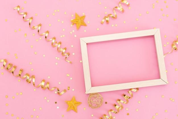 Fotorahmenspott oben mit raum für text, goldene paillettekonfettis auf rosa hintergrund. Premium Fotos