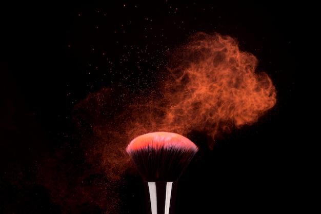 Foundation pinsel mit fliegenden partikeln aus hellem puder Kostenlose Fotos