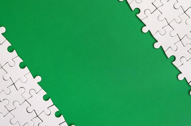 Fragment eines gefalteten weißen puzzles auf dem hintergrund einer grünen plastikoberfläche Premium Fotos