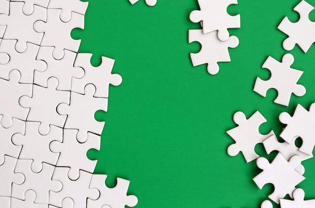 Fragment eines gefalteten weißen puzzles und eines stapels der ungekämmerten puzzlespielelemente gegen den hintergrund Premium Fotos