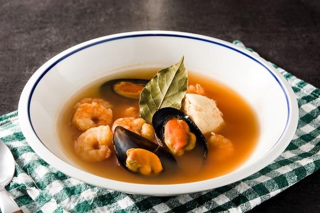Französische bouillabaisse-suppe in der weißen platte auf schwarzem hintergrund. Premium Fotos