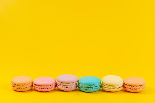 Französische macarons der vorderansicht bunt köstlich und gebacken auf gelbem, kuchenkeks-süßwaren Kostenlose Fotos