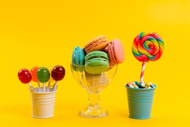 Französische macarons der vorderansicht zusammen mit bonbons und lutschern in eimern auf gelben, zuckersüßen süßwaren Kostenlose Fotos