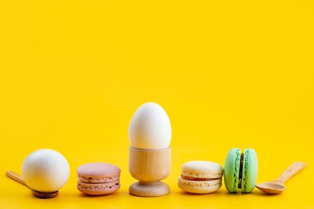 Französische macarons der vorderansicht zusammen mit gekochten eiern auf gelbem kekskuchen-kandiszucker-essen Kostenlose Fotos