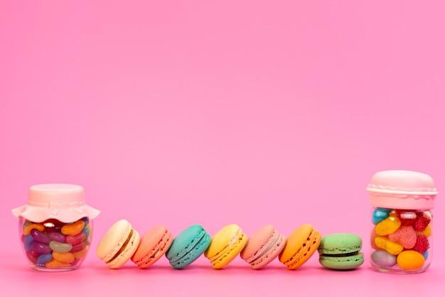 Französische macarons mit frotn-ansicht und mehrfarbigen bonbons in dosen auf pink Kostenlose Fotos