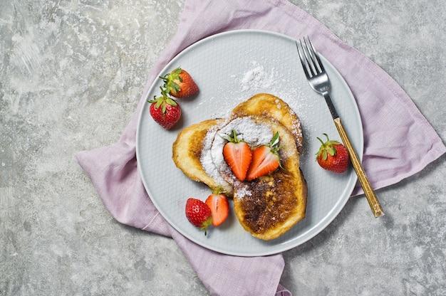 Französischer toast mit erdbeeren und ahornsirup auf einer grauen platte. Premium Fotos