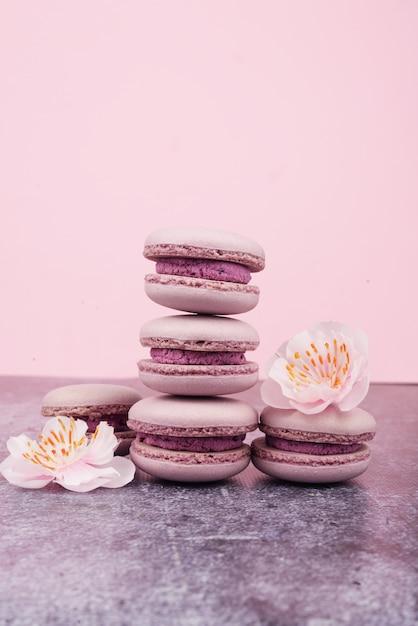 Französisches macaron plätzchen-nachtischrosaflieder auf einem dunklen rosa hintergrund mit rosa blumen Premium Fotos