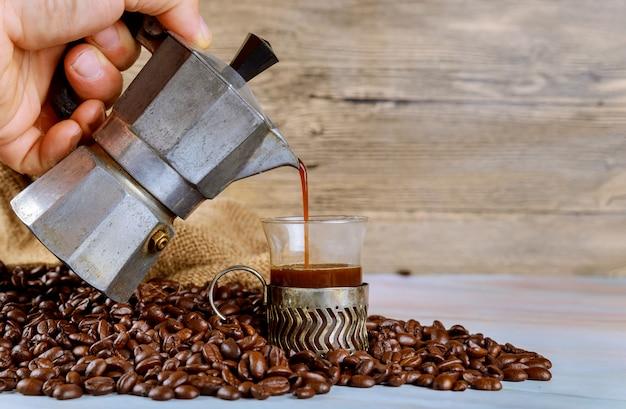 Franzosen gießen kaffee in glasschale espressokaffee in den kaffeebohnen Premium Fotos