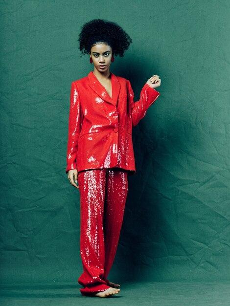 Frau afroamerikaner in glänzenden festlichen modekleidung auf einer farbigen oberfläche, die aufwirft Premium Fotos