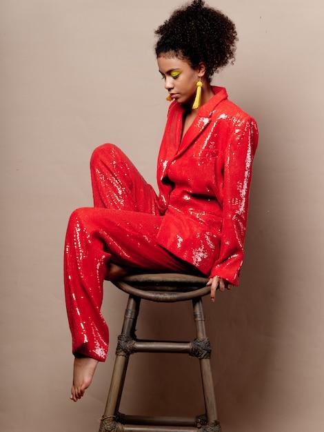 Frau afroamerikaner in glänzenden festlichen modekleidung auf einer farbigen raumaufstellung Premium Fotos