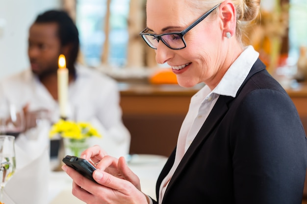 Frau am business-lunch post am telefon überprüfend Premium Fotos