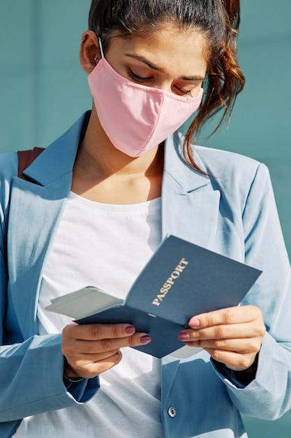 Frau am flughafen mit medizinischer maske, die ihren pass überprüft Kostenlose Fotos