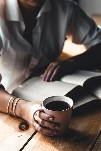 Frau am morgen trinkt kaffee und liest altes buch in einem weißen hemd Premium Fotos