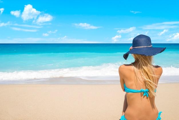 Frau am strand mit blick auf das meer, das sommerferien genießt Kostenlose Fotos