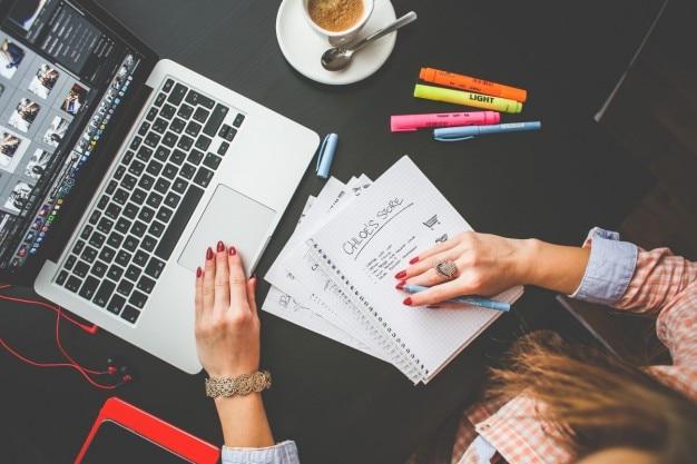 Frau arbeitet an ihrem Schreibtisch Kostenlose Fotos