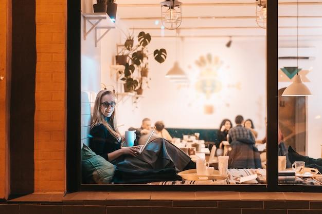 Frau arbeitet in einem café am abend Kostenlose Fotos