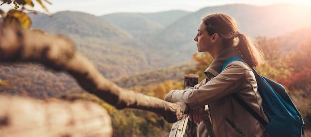 Frau auf dem berg, der den zaun bereitsteht und ansicht genießt Premium Fotos
