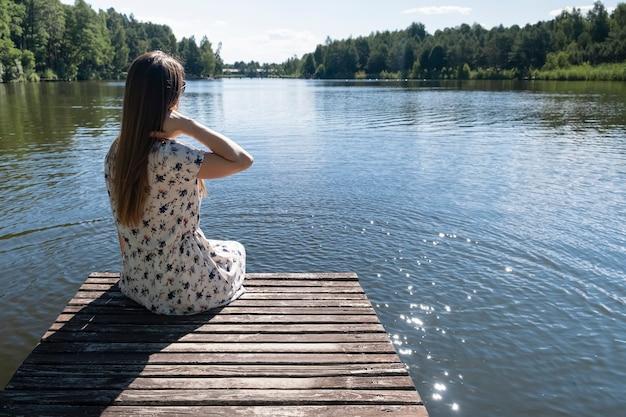 Frau auf dem see. junge frau, die weißes kleid trägt, das natur genießt und auf einem hölzernen pier auf dem see, rückansicht ruht Premium Fotos