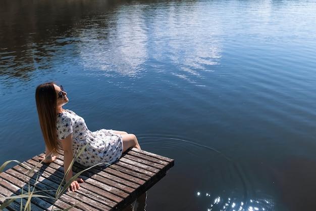 Frau auf dem see. junge frau, die weißes kleid trägt, genießt natur und ruht sich auf einem hölzernen pier auf dem see aus Premium Fotos