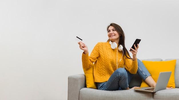 Frau auf dem sofa, das smartphone in einer hand und eine kreditkarte in der anderen hält Kostenlose Fotos