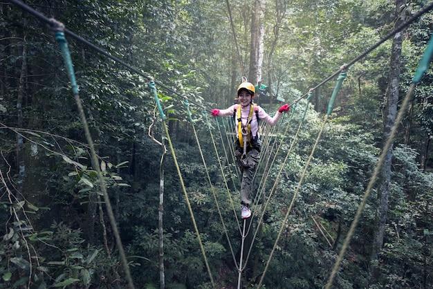 Frau auf kabeln in einem abenteuerpark auf einem schwierigen kurs Premium Fotos