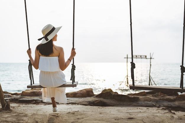 Frau auf schaukel am strand Premium Fotos