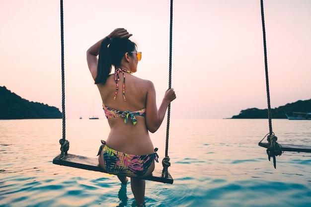 Frau auf schaukel im meer auf tropischer insel Premium Fotos