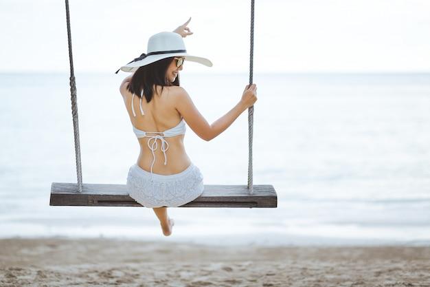 Frau auf schaukel im strand Premium Fotos