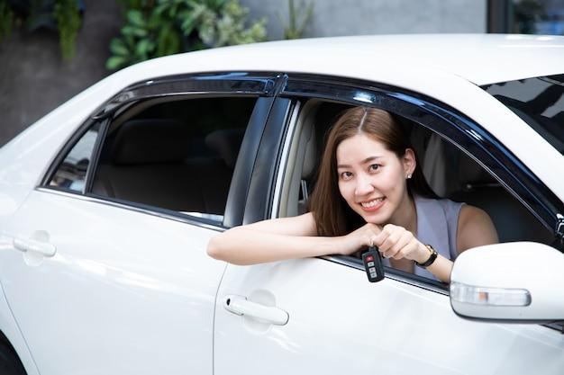 Frau autofahrer lächelnd und zeigt neue autoschlüssel. Premium Fotos