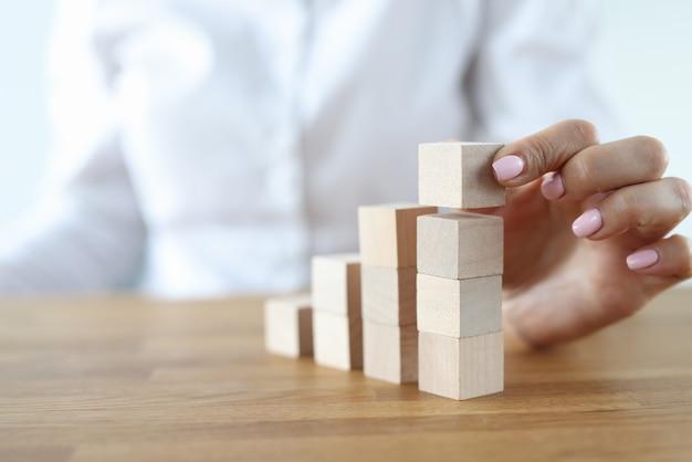 Frau bauen turm aus holzwürfeln auf tisch. karrierewachstum die treppe hinauf Premium Fotos