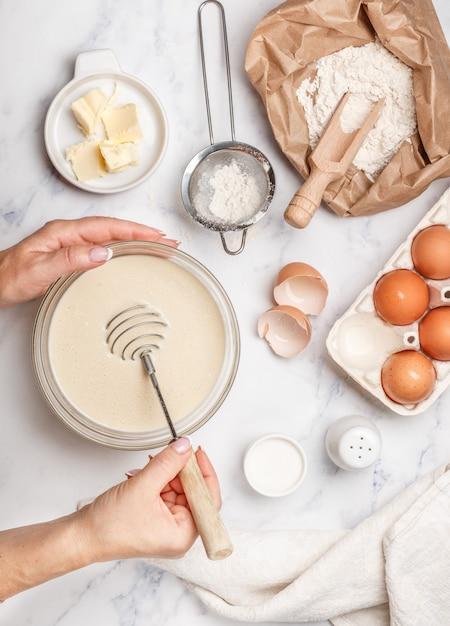 Frau bereitet teig für selbst gemachte pfannkuchen zum frühstück zu, wischen für das schlagen in den händen Premium Fotos