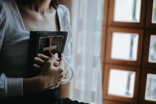 Frau betet mit bibel und holzkreuz an der kirche Premium Fotos