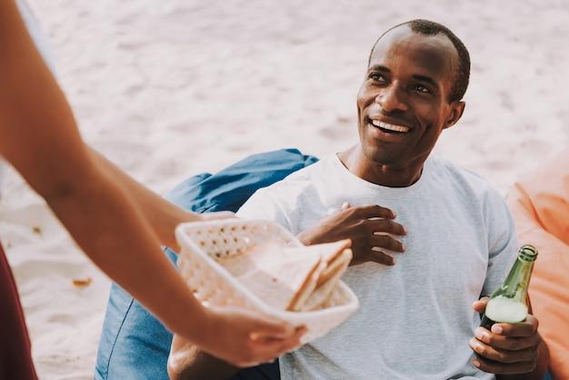 Frau bietet glücklichen kerl auf picknick sandwich an Premium Fotos