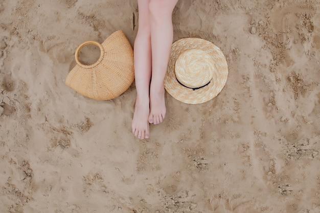 Frau bräunte beine, strohhut und tasche auf sandstrand. mit den füßen im sand am strand entspannen. Premium Fotos