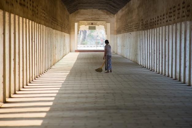 Frau der buddhismus-pilgerfahrtzeremonie mit den besen, die am gehweg shwezigon pagode fegen Premium Fotos