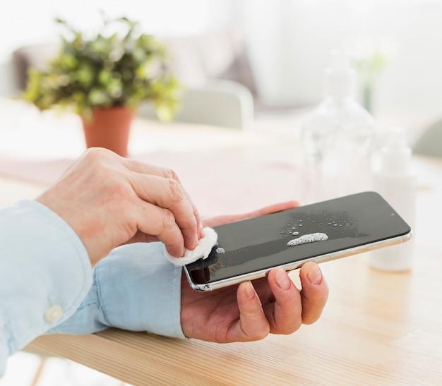 Frau desinfiziert ihr telefon zu hause Kostenlose Fotos