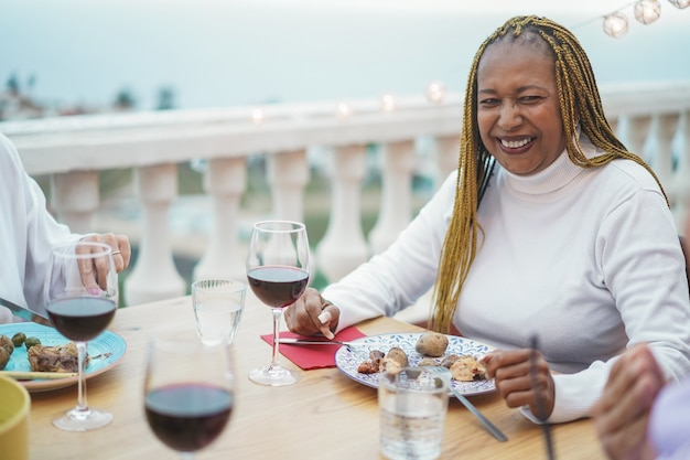 Frau, die abendessen und wein mit freunden am grill im restaurant trinkt Premium Fotos