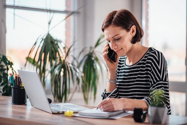 Frau, die am intelligenten telefon im büro spricht Premium Fotos