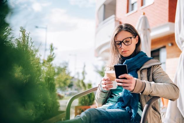 Frau, die am intelligenten telefon schreibt Premium Fotos
