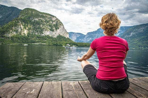 Frau, die am see auf pier in der schönen landschaft mit blick auf berge, see und blauen himmel sich entspannt Premium Fotos