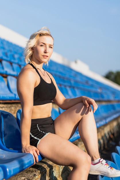 Frau, die am stadion betrachtet kamera sitzt Kostenlose Fotos