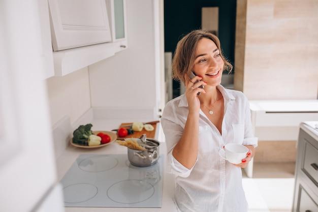 Frau, die am telefon an der küche spricht und frühstück kocht Kostenlose Fotos