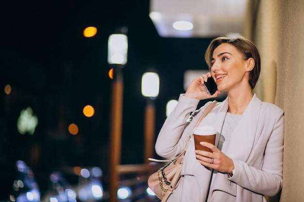 Frau, die am telefon spricht und kaffee draußen in der straße nachts trinkt Kostenlose Fotos