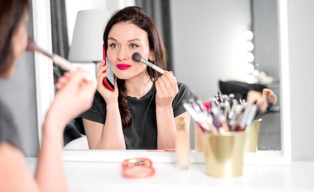 Frau, die am telefon spricht und make-up macht Kostenlose Fotos