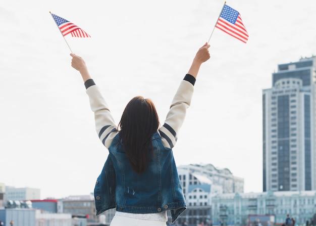 Frau, die amerikanische flaggen in den händen wellenartig bewegt Kostenlose Fotos